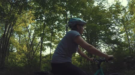 ciclismo : A woman on bike riding in lush green forest