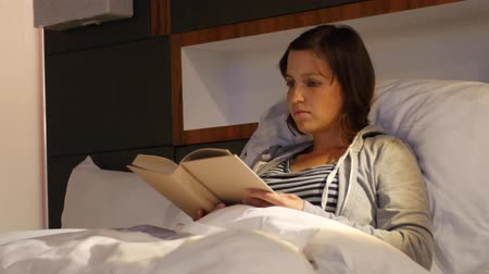 colchão : A woman reading a book in a cozy bed at hotel room Stock Footage