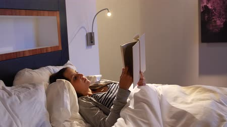 colchão : A woman reading her book in comfortable bed at hotel room Stock Footage