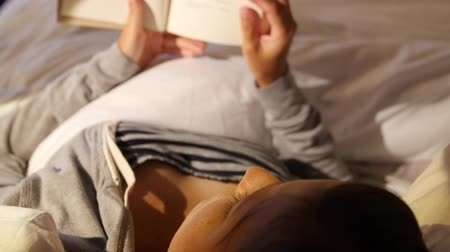 ágynemű : A woman reading her book in a comfortable bed at hotel room