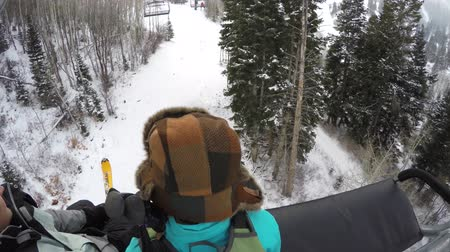 buty : A woman riding on a ski lift on cold day