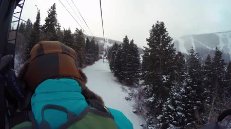 kask : A woman riding on ski lift on cold day