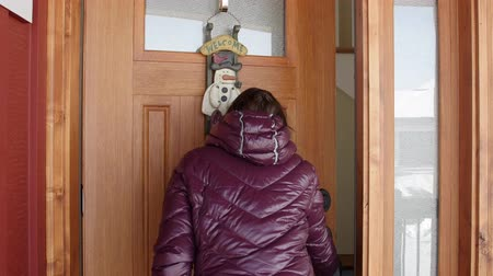 вводить : A woman walks into a house with a welcome sign