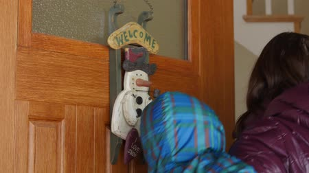 вводить : A woman with baby walks into a house with a welcome sign