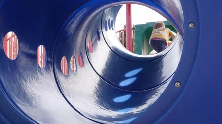 plac zabaw : A young boy playing on slide at the park