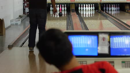 pino : A young family bowls in small town bowling alley