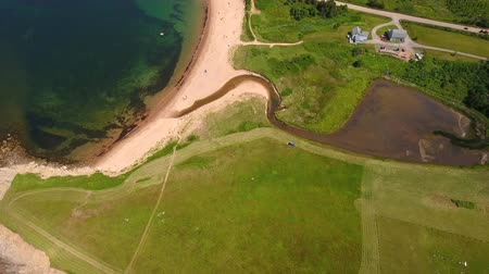 cape breton : Aerial high shot of a farmer cutting grass on a field by ocean cove