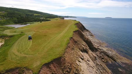 cape breton : Aerial rotating shot as farmer cuts grass on a field by ocean cove Stock Footage