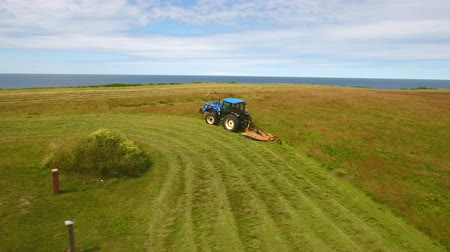 cape breton : Aerial rotating shot farmer cuts the grass on field by ocean cove Stock Footage