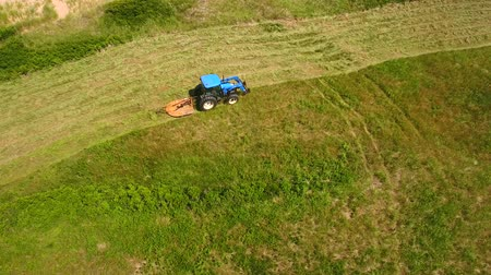 cape breton : Aerial shot a farmer cutting grass on a field by ocean cove