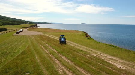 cape breton : Aerial shot farmer cuts the grass on field by ocean cove Stock Footage