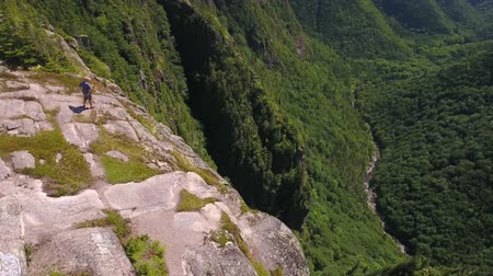 cape breton : Aerial shot of a man above cliff and mountain forest Stock Footage
