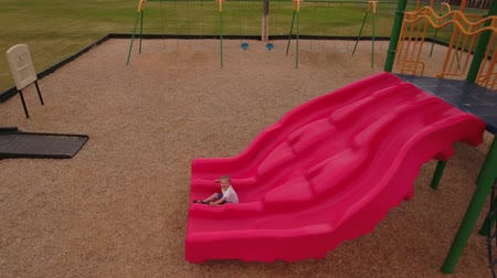 emocje : Aerial shot of boy playing on the city park slide