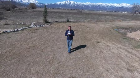 masculino : Aerial shot of man using a remote to fly drone Stock Footage