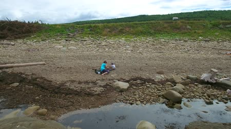 плодородный : Aerial shot of mother playing with toddler on rocky beach Стоковые видеозаписи