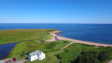 mohás : Aerial shot over cottages on Cape Breton coastline with beach Stock mozgókép