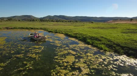 mohás : Aerial travelling shot of two boys rowing a boat in pond Stock mozgókép
