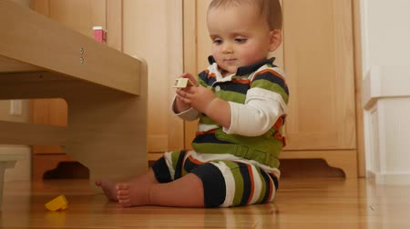 otcovství : An adorable little baby boy playing in living room on floor