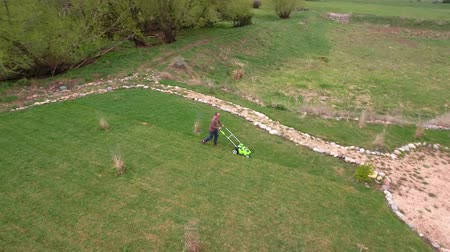 crescimento : An aerial view of a man mowing the lawn