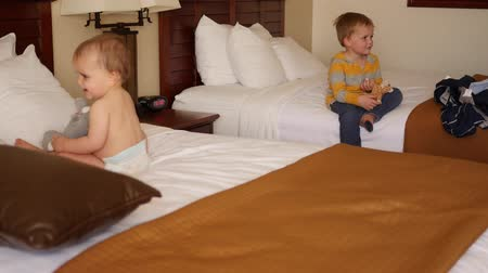 colchão : An interior panning shot of cute boys on hotel room bed Stock Footage
