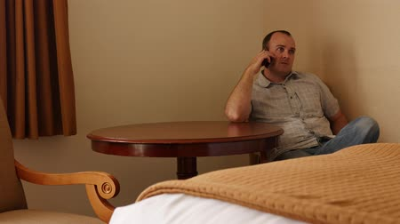 colchão : An interior shot of a man on phone in hotel room Stock Footage