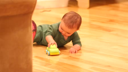 ailelerin : Baby playing on hardwood floor with a car