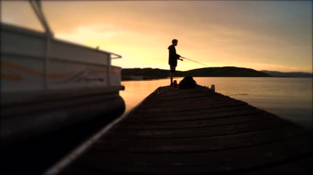 chaluha : Boy fishing with a pole off a dock at sunse Dostupné videozáznamy