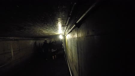 underground tunnel : Camera moving shot through a dark coal mine in glace bay with tourists
