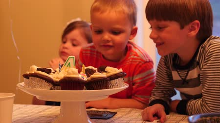 jíst : Children eating cupcakes for a birthday party celebration