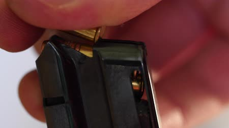 mass shooting : Closeup man loads bullets into magazine Stock Footage