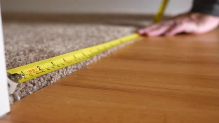 palce : Closeup shot of a man measuring floor with measuring tape