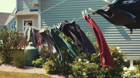 varal : Clothes hang on a line blowing in a wind