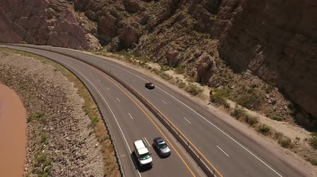 nevada : Cool aerial shot cars driving in a desert canyon by river