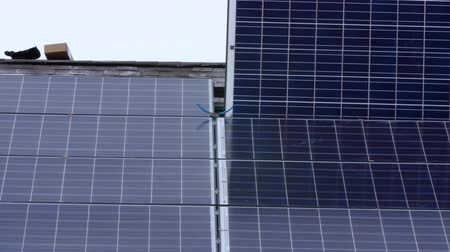fotovoltaik : Crews placing solar panels on the roof of a house Stok Video