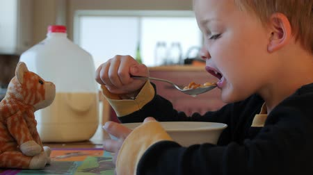 jíst : Cute boy eats cereal with stuffed animal Dostupné videozáznamy