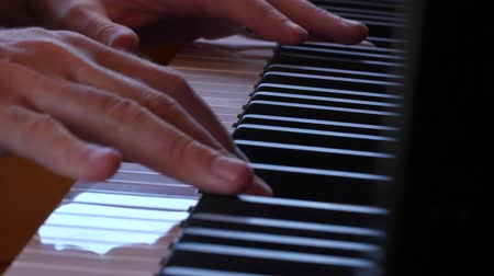 martelo : Dolly shot fingers playing keys of beautiful black grand piano
