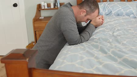 ajoelhado : Dolly shot of a man praying by his bedside