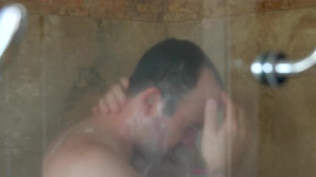 skóra : Dolly shot of a man washing hair in shower Wideo