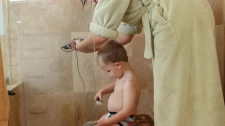 grzebień : Dolly shot of a mother cutting boys hair in shower