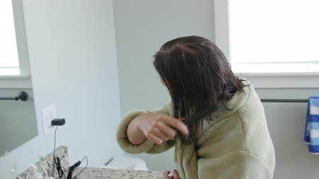 dryer : Dolly shot of a woman brushing wet hair in a robe Stock Footage