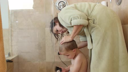 grzebień : Dolly shot of a woman cutting boys hair in shower