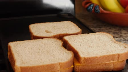 cozinhar : Dolly shot of woman cooking grilled cheese sandwiches