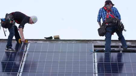 солнечный : Editorial a crew placing solar panels on the roof