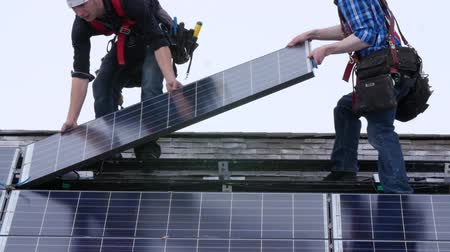устанавливать : Editorial a crew placing solar panels on roof Стоковые видеозаписи