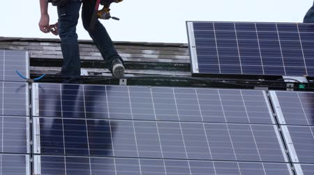 солнечный : Editorial a crew placing solar panels on the roof of house