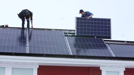 солнечный : Editorial crew placing solar panels on the roof of house