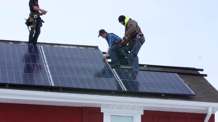 fotovoltaik : Editorial crews placing solar panels on a roof of a house