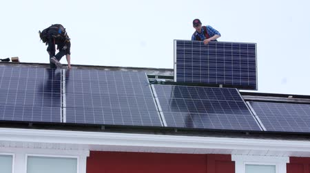 fotovoltaik : Editorial crews placing solar panels on the roof of a house Stok Video