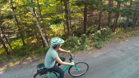 ciclismo : Fun high shot of woman biking in a green forest on bike trail