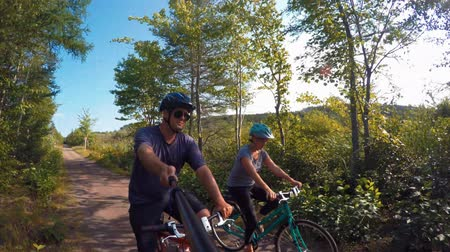 alpy : Fun shot of a couple biking in a green forest on bike trail